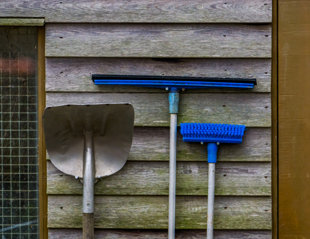 Stable cleaning equipment hanging on a wooden wall