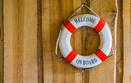 life buoy with the text welcome on board, nautical and travel background Фото со стока