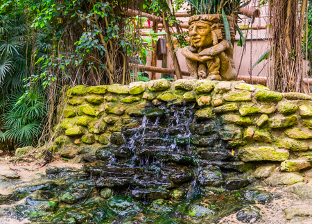 Waterfall in a tropical garden, streaming water over some rocks, stone sculpture decoration