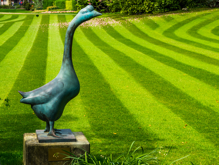 marble goose statue with a fresh mowed grass lawn with stripes, Modern luxurious gardens
