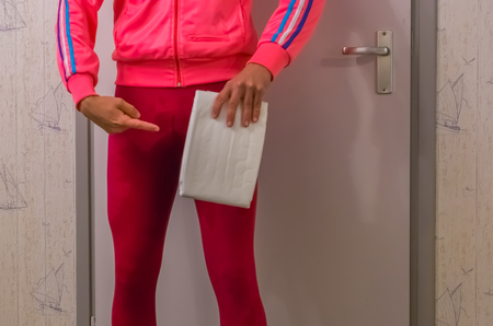 young lady in a wet legging holding and pointing at a white adult diaper, urinary incontinence issues, embarrassing medical problems Banque d'images