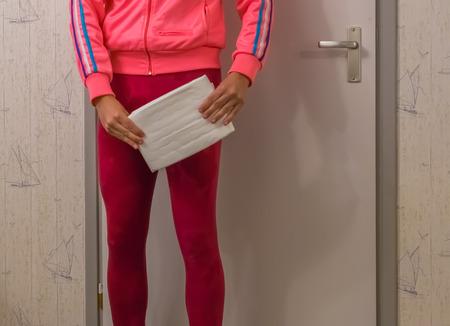Incontinencia urinaria, señorita en un legging mojado sosteniendo un pañal blanco para adultos, problemas de salud vergonzosos