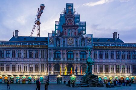 The city hall of antwerp with monumental statue lighted at night, grotemarkt, Antwerpen, Belgium, April 23, 2019