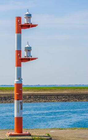 red with white striped light pole at the harbor of Tholen, lamppost for the ships
