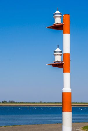 light pole for the ships at the harbor of tholen, Red with white striped lamppost