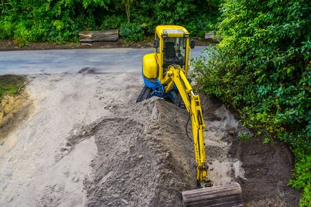 yellow Excavator with a heap of sand, earthmoving industry, digger machine for moving sand