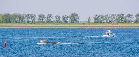 Boats sailing at the beach of tholen, recreational water sports, Zeeland, the netherlands
