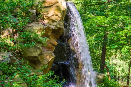 waterfall streaming of a cliff in a forest, nature background, garden architecture