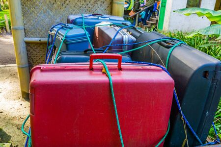 Old luggage cart filled with suitcases that are secured, nostalgic baggage transportation