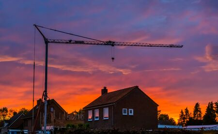 big construction crane during sunset, building site of a house in the village of Rucphen, Architecture of the netherlands