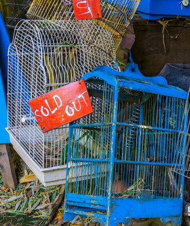 bird cages in closeup with sold out sign, Pet trade in Asia, Animal shop background