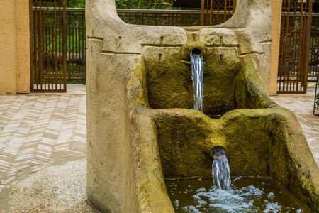 old vintage water fountain with streaming water, historical village architecture