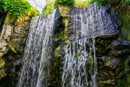 multiple waterfalls streaming of a big rock cliff in a forest, nature background