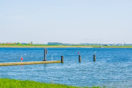 small jetty in tholen city with boats sailing on the water, Scenery of the Oosterschelde, Bergse diepsluis, Zeeland, The Netherlands
