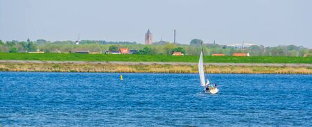 ship sailing on the oosterschelde with the city scenery in the background, Tholen, Zeeland, The netherlands