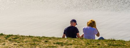 male and female couple sitting at the water side of tholen beach, Bergse diepsluis, Zeeland, The netherlands