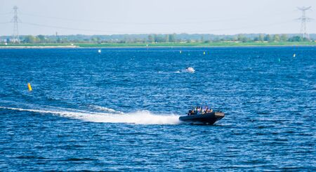 people sailing in a speedboat on the oosterschelde of tholen, Touristic water sport and transportation, popular city in zeeland, The Netherlands