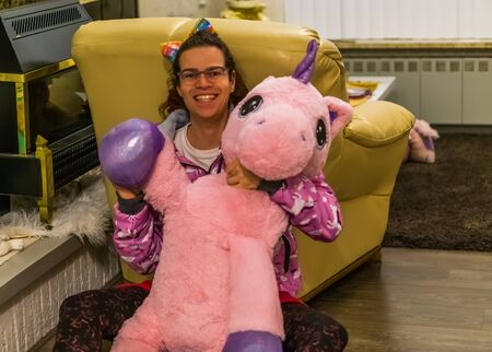 very funny and cute portrait of a transgender girl holding a stuffed unicorn and waving, LGBT Diversity