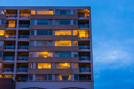 Apartments complex with lighted windows in the evening, modern city architecture in tilburg, The Netherlands Stockfoto