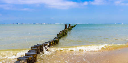 beautiful ocean view with wooden poles on breskens beach, vlissingen in the distance, Zeeland, the Netherlands 免版税图像