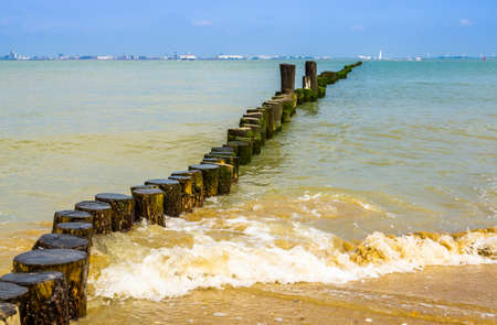 the ocean with waves hitting wooden poles on the beach of breskens, Zeeland, The Netherlands 版權商用圖片