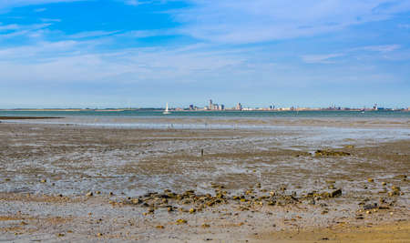 Breskens beach mudflats with view on vlissingen city, Zeeland, The Netherlands 免版税图像