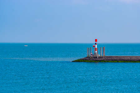 pier with small lighthouse and blue ocean, scenery of the harbor of Breskens, Zeeland, The Netherlands