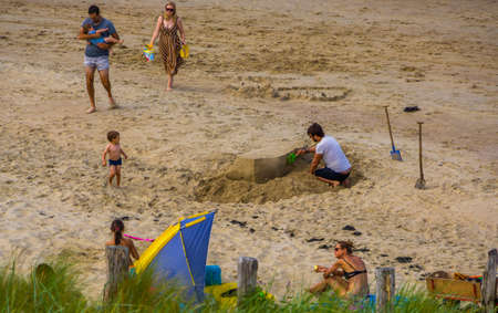 adult man playing in the sand on the beach, Breskens, Zeeland, The Netherlands, 20 July, 2020