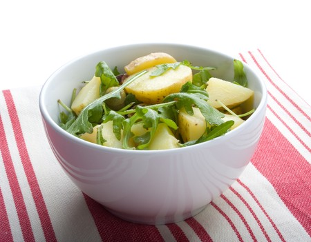 rocket lettuce: Gourmet potato salad with ruccola lettuce (rocket lettuce), on red and white tablecloth