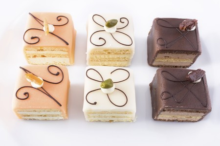 Close up of six petits fours on white plate. Stock Photo