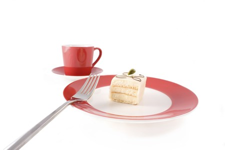 cup four: Petit four on red and white plate with fork and red coffee cup.  Isolated on white.