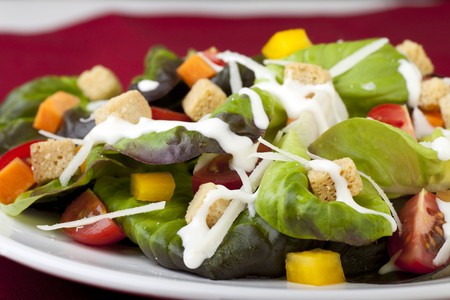 Fresh green salad with tomatoes croutons and creamy dressing. Stock Photo