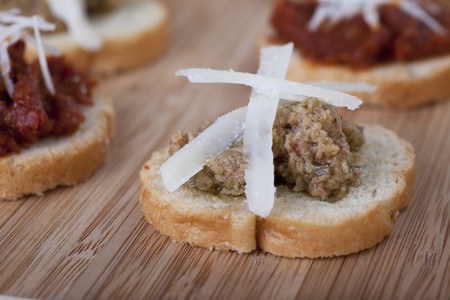 Grean olive tapenade on lightly toasted baguette slices toped with fresh shredded Parmesan cheese.
