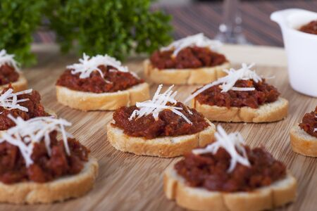 Fresh homemade sun dried tomato tapenade on toasted baguette topped with fresh grated cheese. Stock Photo