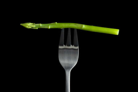 Raw asparagus on fork with black background. Stock Photo