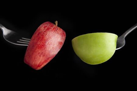 granny smith apple: Fuji and granny smith apple slices on forks with black background.