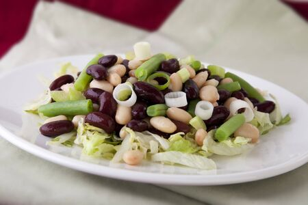 Three bean salad with cannellini, kidney and green beans, on a bed of iceberg lettuce.