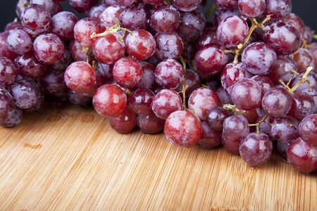 concord grape: Moist red grapes on cutting board.