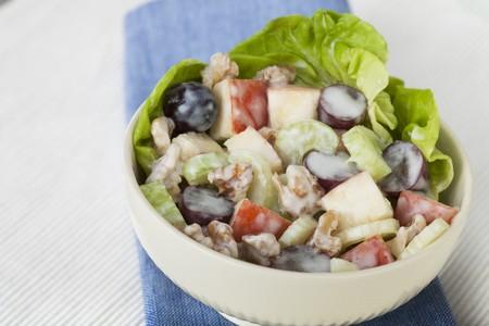 Bowl of Waldorf salad on blue napkin.