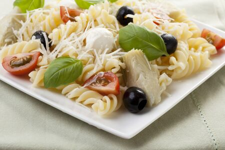 Fusilli pasta with black olives, mozzarella cheese, artichoke hearts and tomato slices, topped with fresh basil leaves.