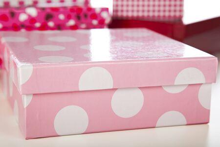 Decorative pink and while polka dot gift box closeup. photo