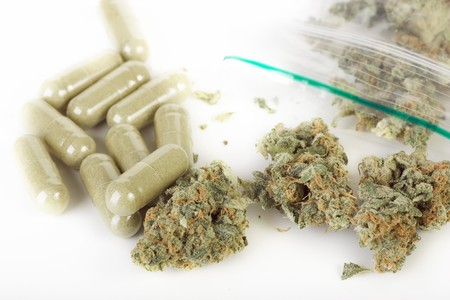 Plastic baggie of dried marijuana and green capsules.
