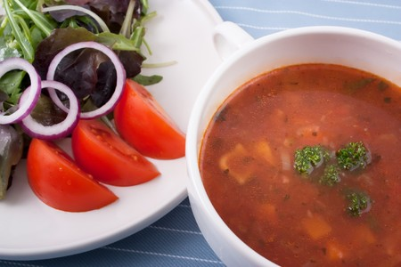 soup bowl: Minestrone soup and a side salad with greens onions and tomatoes for a great low calorie and nutritious lunch.