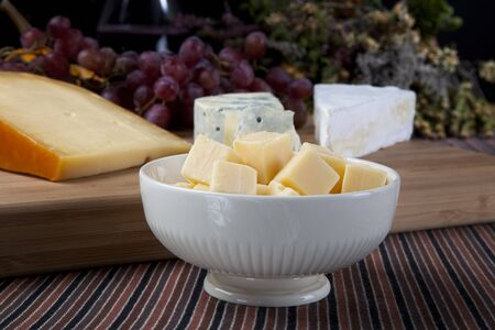 Cheese cubes in a bowl on a table with cheese  and grapes in the background.