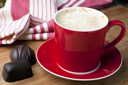 Fresh latte and two gourmet chocolates for a well deserved break. Stock Photo - 7963691