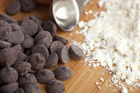 Chocolate chips, flour and a measuring spoon ready for making cookies. Stock Photo