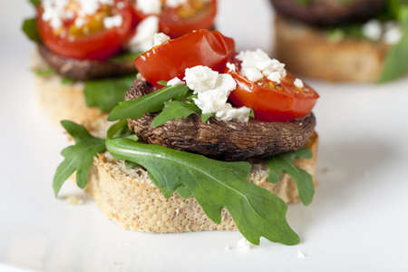 Shitake mushroom tapas with cherry tomatoes and crumbled  feta cheese. Stock Photo
