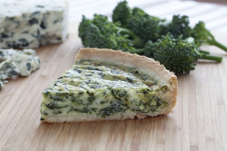 Slice of blue cheese and broccoli quiche with ingredients in background