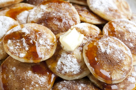 Dutch mini pancakes, or poffertjes, with butter, syrup and powdered sugar.  background. Stock Photo