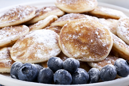 Dutch mini pancakes, or poffertjes, and fresh blueberries sprinkled with powdered sugar.